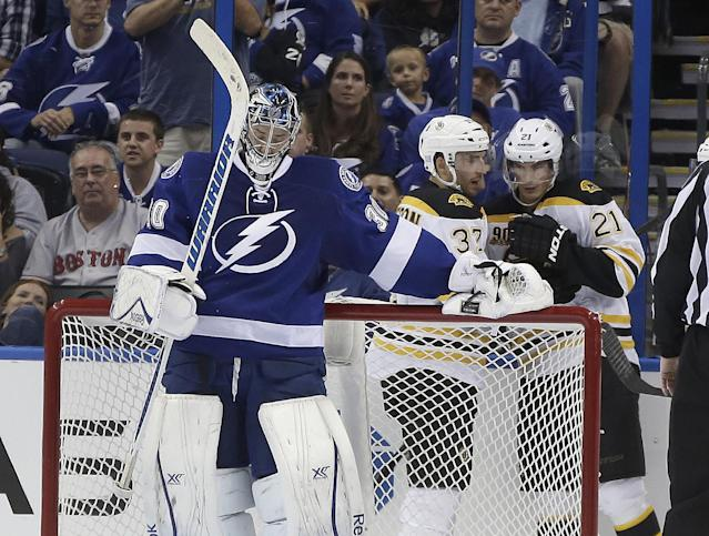 Tampa Bay Lightning goalie Ben Bishop (30) swings his stick as Boston Bruins center Patrice Bergeron (37) celebrates with teammate Loui Eriksson (21), of Sweden, after Bergeron scored a goal during the second period of an NHL hockey game Saturday, Oct. 19, 2013, inTampa, Fla. (AP Photo/Chris O'Meara)