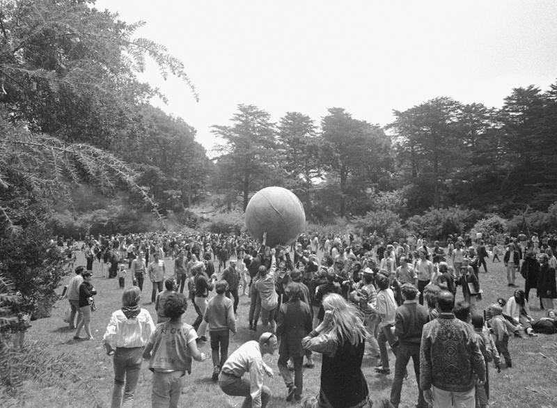 """FILE - In this June 21, 1967, file photo, people keep a large ball, painted to represent a world globe, in the air during a gathering at Golden Gate Park in San Francisco, to celebrate the summer solstice, Day 1 of the """"Summer of Love."""" Golden Gate Park turned 150 years old on Saturday, April 4, 2020, and the huge party to celebrate San Francisco's beloved treasure will, for the time being, take place online. (AP Photo/File)"""