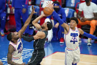 Brooklyn Nets' Bruce Brown, center, goes up for a shot against Philadelphia 76ers' Shake Milton, left, and Matisse Thybulle during the second half of an NBA basketball game, Wednesday, April 14, 2021, in Philadelphia. (AP Photo/Matt Slocum)
