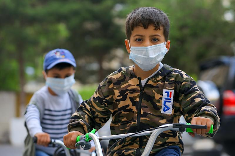 BAKU, AZERBAIJAN - MAY 21: A boy rides a bicycle with a protective mask after Azerbaijani government started to ease some restrictions caused by the novel coronavirus (COVID-19) pandemic on May 21, 2020 in Baku, Azerbaijan. The coronavirus outbreak has infected more than 5 million people across the world. Azerbaijan has reported 3749 cases of COVID-19 and 44 deaths.(Photo by Aziz Karimov/Getty Images)