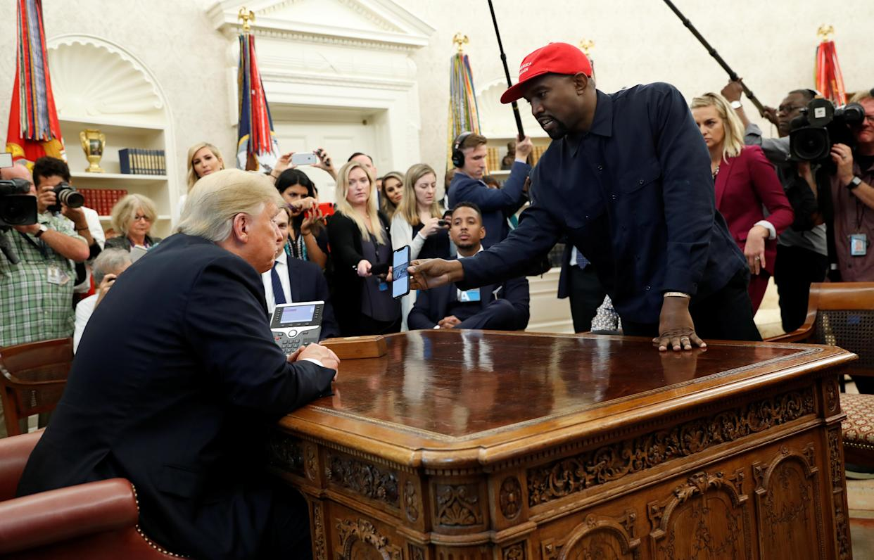 Rapper Kanye West shows President Trump his mobile phone during a meeting in the Oval Office at the White House Thursday. (Photo: Kevin Lamarque/Reuters)