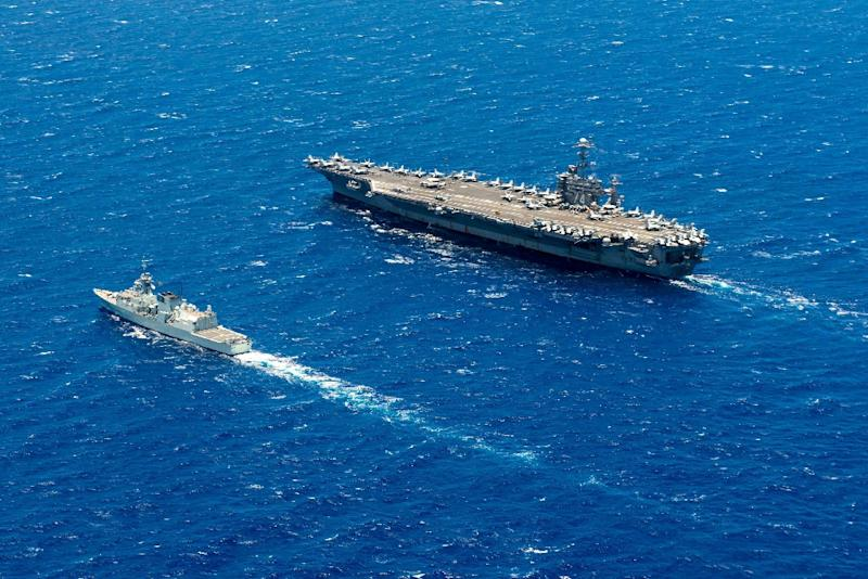 A Royal Canadian Navy frigate steams alongside the USS John C. Stennis during the 2016 Rim of the Pacific maritime exercise