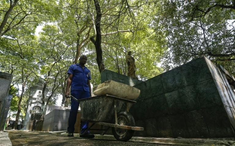 The rampant death in Brazil during the coronavirus pandemic often overwhelmed Osmair Candido, but the gravedigger says he took strength from philosophers like Nietzsche and Kierkegaard (AFP/Miguel SCHINCARIOL)