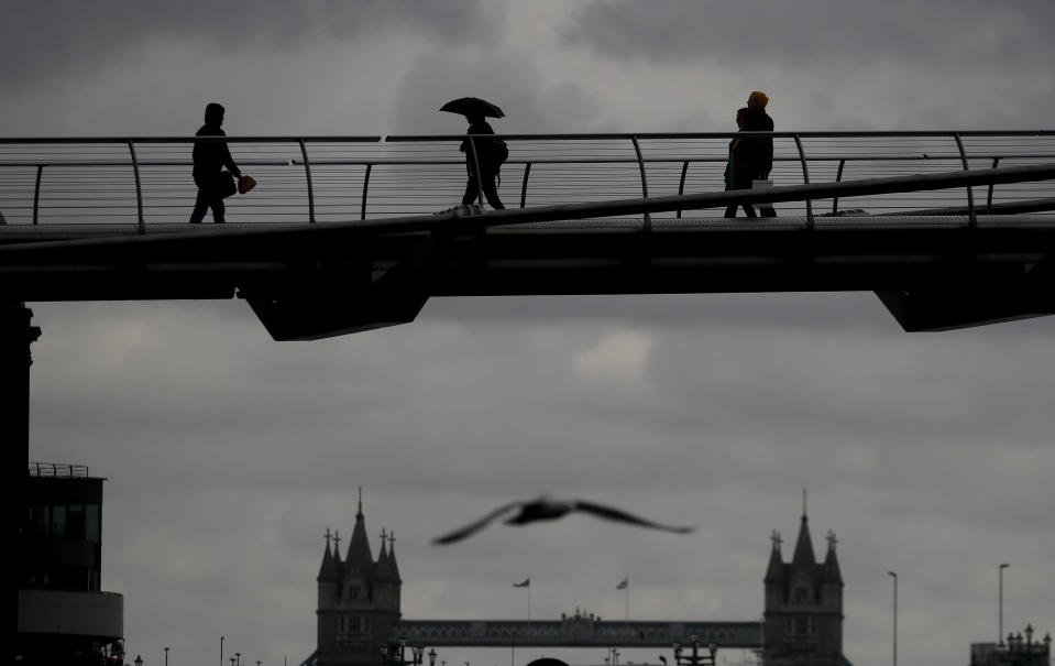 People are silhouetted as they walk over Millennium Bridge during rainy weather, as the coronavirus lockdown continues in London, Thursday, March 25, 2021. (AP Photo/Kirsty Wigglesworth)