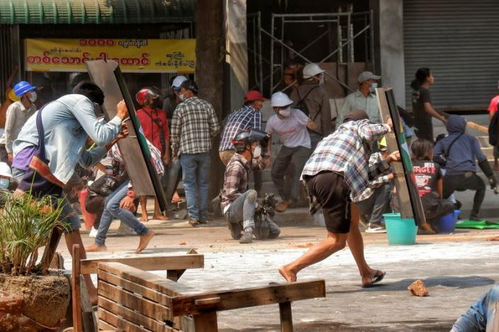 Protesters cover with makeshift shields during an anti-coup protest in Mandalay, Myanmar