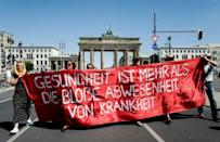 """Marchers unveil a banner reading """"health is more than the simple absence of illness"""""""