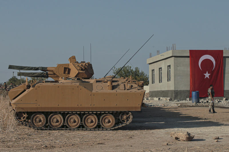 Turkish army personnel carriers are parked on a road towards the border of Syria in Sanliurfa province, Turkey, Monday, Oct. 14, 2019. Syrian troops entered several northern towns and villages Monday, getting close to the Turkish border as Turkey's army and opposition forces backed by Ankara marched south in the same direction, raising concerns of a clash between the two sides as Turkey's invasion of northern Syria entered its sixth day. (AP Photo/Emrah Gurel)