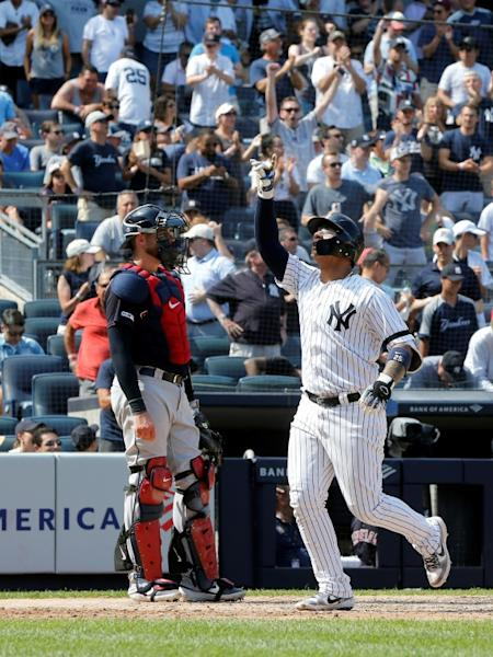 New York's Gleyber Torres reacts at home plate after his sixth inning home run Cleveland's Kevin Plawecki looks on