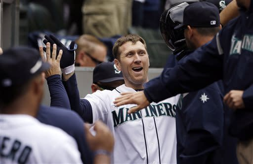 Seattle Mariners' Jason Bay is congratulated after hitting a home run against the Los Angeles Angels in the seventh inning of a baseball game, Sunday, April 28, 2013, in Seattle. (AP Photo/Elaine Thompson)