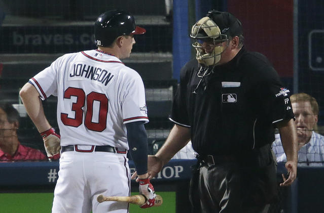 Atlanta Braves' Elliot Johnson (30) speaks to the umpire about a call in the fifth inning of Game 1 of the National League Divisional Series against the Los Angeles Dodgers, Thursday, Oct. 3, 2013, in Atlanta. (AP Photo/Dave Martin)