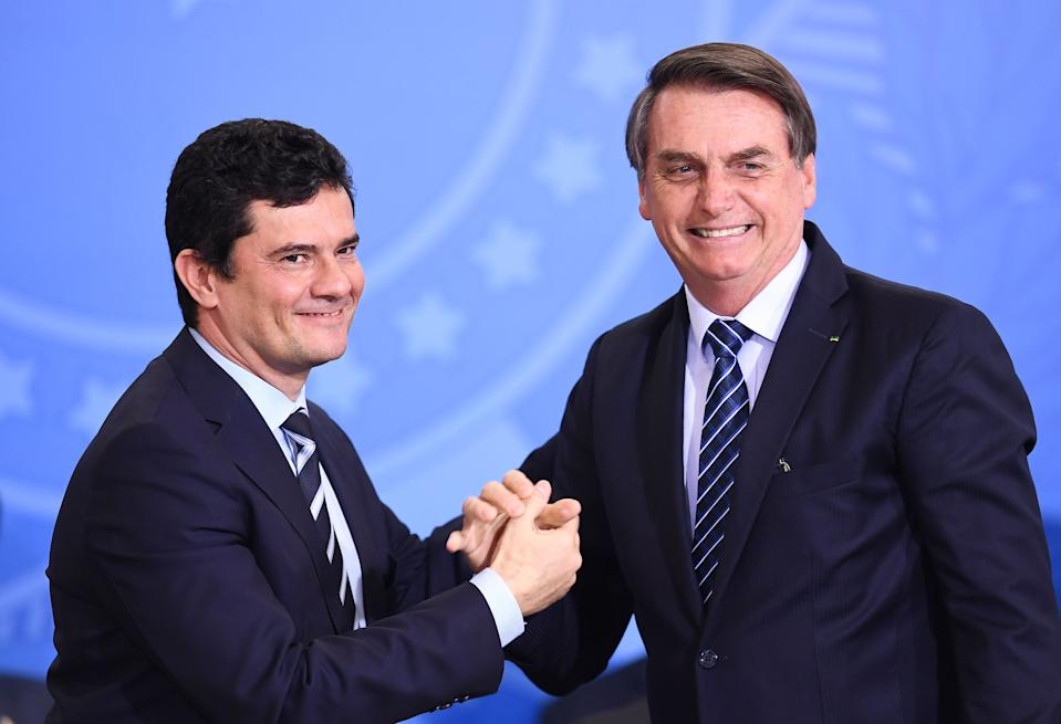 Brazilian President Jair Bolsonaro (R) and his Minister of Justice and Public Security Sergio Moro shake hands during the launching ceremony of the Front Brazil Project, which aims at reducing the rates of violence in cities, at Planalto Palace in Brasilia, on August 29, 2019. (Photo by EVARISTO SA / AFP)        (Photo credit should read EVARISTO SA/AFP via Getty Images)