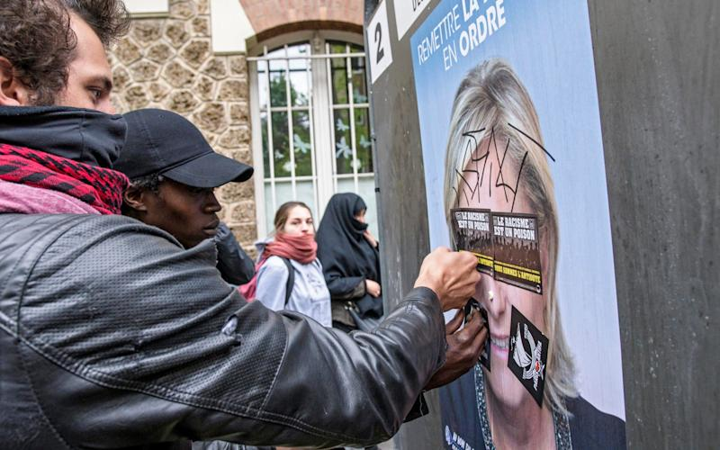 rotesters put stickers on a Marine Le Pen's campaign poster during a protest against far-right Front National (FN) party in Paris