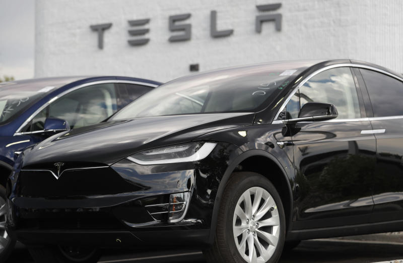 FILE- In this July 8, 2018, file photo, a 2018 Model X sits on display outside a Tesla showroom in Littleton, Colo. While Tesla grapples with internal issues like production delays, a sometimes-erratic CEO and a recent about-face on whether to go private, its rivals are moving aggressively into the luxury electric vehicle space. (AP Photo/David Zalubowski, File)
