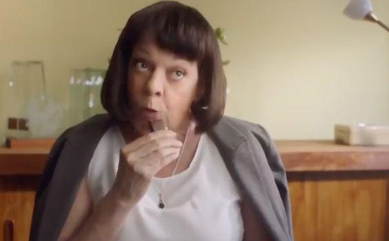 """""""Darrell Lea Makes it Better"""" ad actress Deborah Kennedy takes a bite of chocolate after asking her employee, Jan, where their ad is in """"the directory"""". Source: Youtube."""