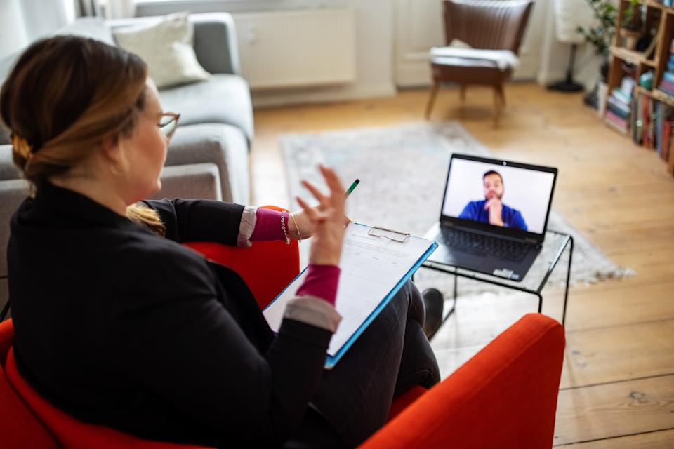 Female psychotherapist talking with a man via online video chat.  Psychologist conducting an online therapy session with her patient.