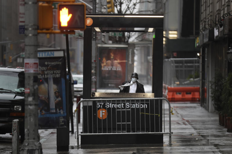 FILE - In this April 13, 2020 file photo, a man enters the subway on a rainy day in New York. New York City transit officials said they're providing buses for homeless people to shelter from unseasonably frigid temperatures this weekend during newly instituted overnight subway closures. The subway system has been shutting down from 1 to 5 a.m. since Wednesday, May 6,  as part of an outbreak-related plan for daily train disinfecting. (AP Photo/Seth Wenig, File)