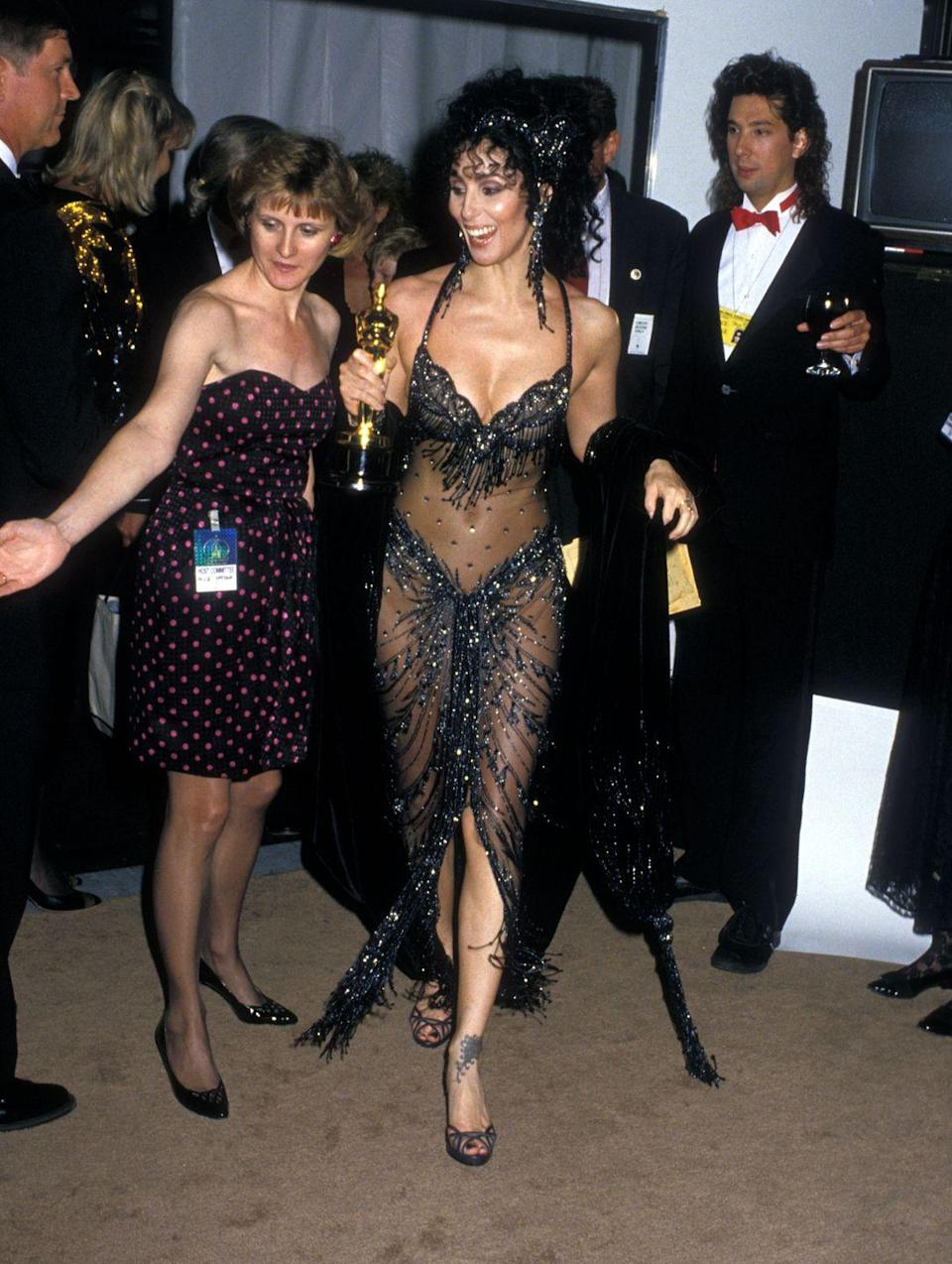<p>The reigning queen of serving iconic looks was extra bold this year in a sheer Bob Mackie design that showed off, well, everything. To make the night even better, the star accepted the Best Actress award for her performance in <em>Moonstruck.</em></p>