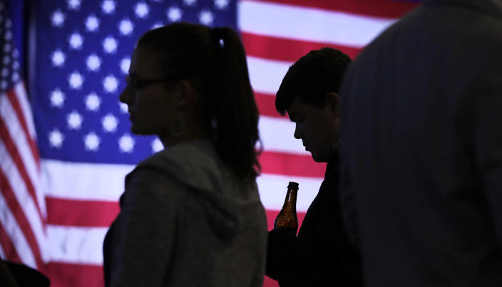 <p>Connor Stubbs of Decatur, Ga., who volunteered for Democratic candidates including Hillary Clinton and New Hampshire Democratic Senate candidate, Gov. Maggie Hassan, holds a beer as he looks down at his cell phone while monitoring election returns during an election night rally in Manchester, N.H., Nov. 8, 2016. (Photo: Charles Krupa/AP) </p>