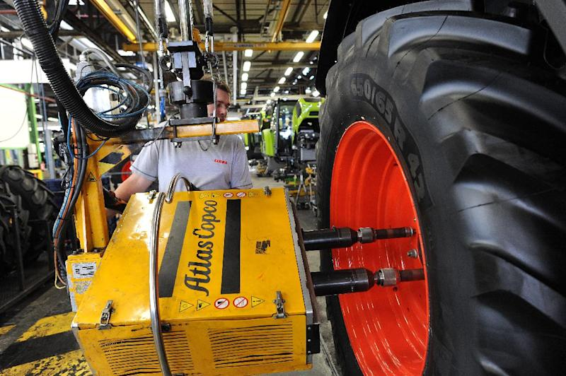 A worker adjusts the back wheel of a tractor on the assembly line of the Claas tractor manufacturer plant in Le Mans, western France, on July 21, 2014 (AFP Photo/Jean-Francois Monier)