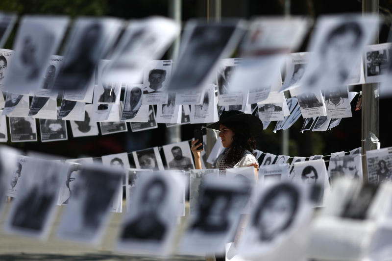 Framed by images of people who have been disappeared, a woman takes photos during a Mother's Day march in Mexico City, Friday, May 10, 2019. Mothers and other relatives of persons gone missing in the fight against drug cartels and organized crime are demanding that authorities locate their loved ones. (AP Photo/Eduardo Verdugo)