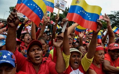 Supporters of Venezuelan President Nicolas Maduro take part in a rally in Caracas on Monday - Credit: FEDERICO PARRA/AFP