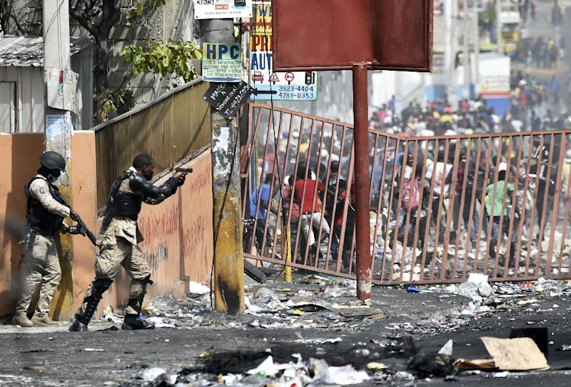 A member of the Haitian police points his gun at people to discourage looting and disperse fresh protests in a commune of the capital (AFP Photo/HECTOR RETAMAL)