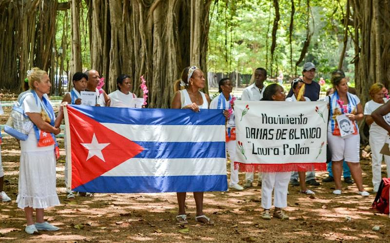 Cuban dissidents and members of the Ladies in White human rights group hold a national flag and pictures of imprisoned dissidents as they protest against the reopening of the US embassy on the island, in Havana, on August 9, 2015 (AFP Photo/Francisco Jara)