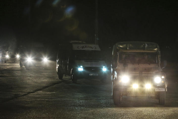 In this late Friday, Oct. 18, 2019 photo, Turkish police and army cars escort vans and buses returning from Syria, reportedly carrying IS group members and their families, at the border town of Akcakale, Sanliurfa province, southeastern Turkey. Turkey's interior minister Suleyman Soylu said Saturday, Oct. 19, that 41 Islamic State members were re-captured in Syria and private IHA news agency said the Turkish nationals among the re-captured were brought over to Turkey in vans. Turkey's President Recep Tayyip Erdogan Erdogan said the Turks captured would be imprisoned and tried in Turkey. (AP Photo/Emrah Gurel)