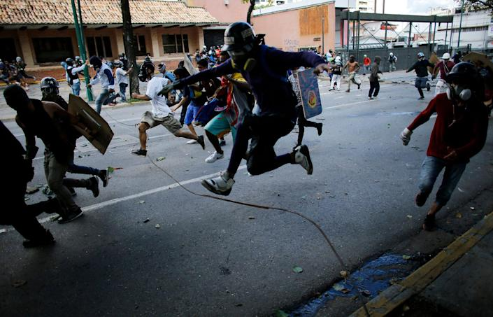<p>Anti-government protesters run from advancing Venezuelan Bolivarian National Guard officers on the first day of a 48-hour general strike in protest of government plans to rewrite the constitution, in Caracas, Venezuela, Wednesday, July 26, 2017. (Photo: Ariana Cubillos/AP) </p>
