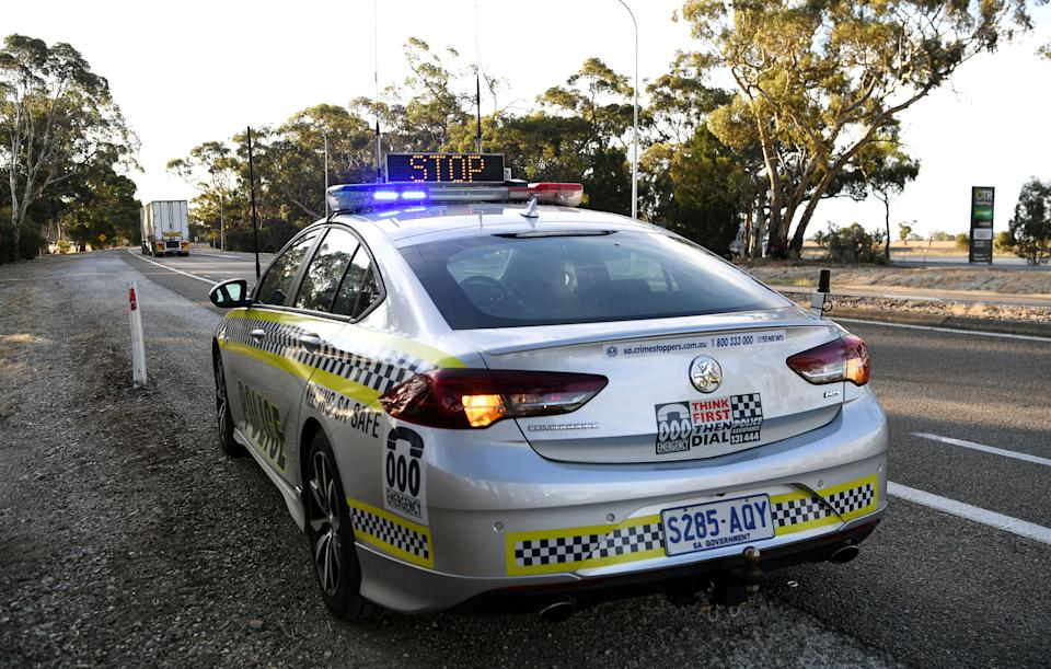 A police car is seen whilst motorists fill out paperwork for police as they cross back into South Australia from Victoria during the coronavirus disease (COVID-19) outbreak, in Bordertown, Australia, March 24, 2020. REUTERS/Tracey Nearmy