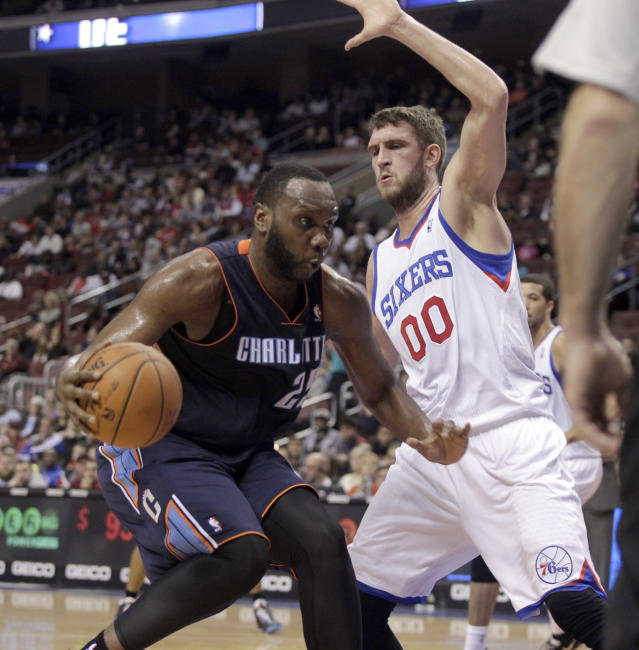 Charlotte Bobcats' Al Jefferson (25) drives into the lane as Philadelphia 76ers' Spencer Hawes (00) defends in the first half of an NBA basketball game, Wednesday, Jan. 15, 2014 in Philadelphia. (AP Photo/H. Rumph Jr.)