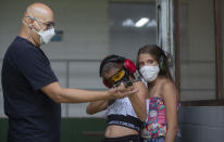 Instructor Robson de Oliveira trains his 10-year-old twin daughters Lorena, center, and Lara, how to properly shoot a firearm at a shooting range in Americana, in the Sao Paulo state of Brazil, Saturday, March 6, 2021. As authorized by two of the most divisive presidential decrees, average Brazilians will be able to own six guns, up from four currently, and carry two simultaneously. (AP Photo/Andre Penner)