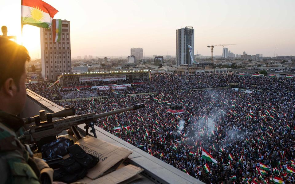 A peshmerga fighter stands watch on a roof as the Iraqi Kurdish leader (unseen) addresses the crowd during a rally to urge people to vote in the upcoming independence referendum in Arbil, the capital of the autonomous Kurdish region of northern Iraq, on September 22, 2017. Iraqi Kurdish leader Massud Barzani insisted that a controversial September 25 independence referendum for his autonomous Kurdish region in northern Iraq will go ahead, even as last-minute negotiations aimed to change his mind. / AFP PHOTO / Mauricio MORALESMAURICIO MORALES/AFP/Getty Images - MAURICIO MORALES/AFP