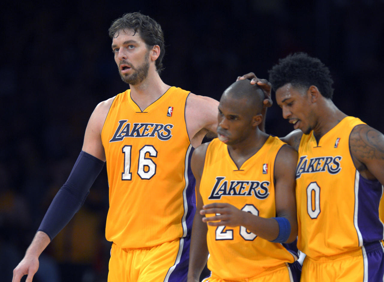 Los Angeles Lakers center Pau Gasol, left, of Spain, guard Jodie Meeks, center, and forward Nick Young celebrate in the closing seconds of an NBA basketball game against the Utah Jazz, Friday, Jan. 3, 2014, in Los Angeles. (AP Photo/Mark J. Terrill)