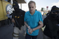 FILE - In this Dec. 5, 2017 file photo, Eric Conn is escorted by SWAT team agents prior to his extradition, at the Toncontin International Airport, in Tegucigalpa, Honduras. The former clients of Conn, who orchestrated a $500 million Social Security fraud remain entangled in a legal mess. Many of Conn's former clients who had their disability benefits restored are getting letters from the Social Security Administration(AP Photo/Moises Castillo, File )