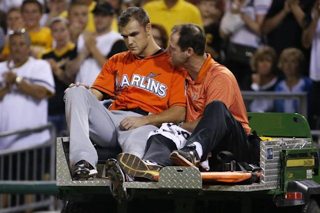 Miami Marlins relief pitcher Dan Jennings, left, rides off the field with a team trainer after being hit by a line drive off the bat of Pittsburgh Pirates' Jordy Mercer during the seventh inning of a baseball game in Pittsburgh Thursday, Aug. 7, 2014. The Pirates won 7-2. (AP Photo/Gene J. Puskar)