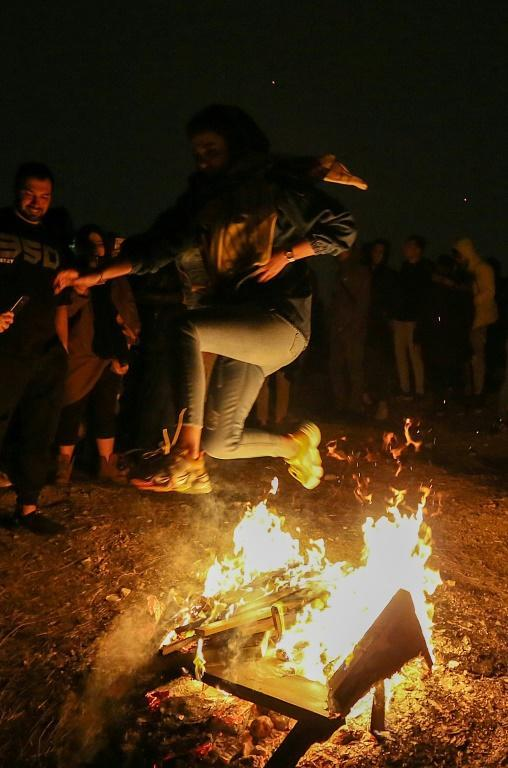 An Iranian jumps over a bonfire in Tehran, part of the traditional celebrations to ward off evil spirits for the coming year