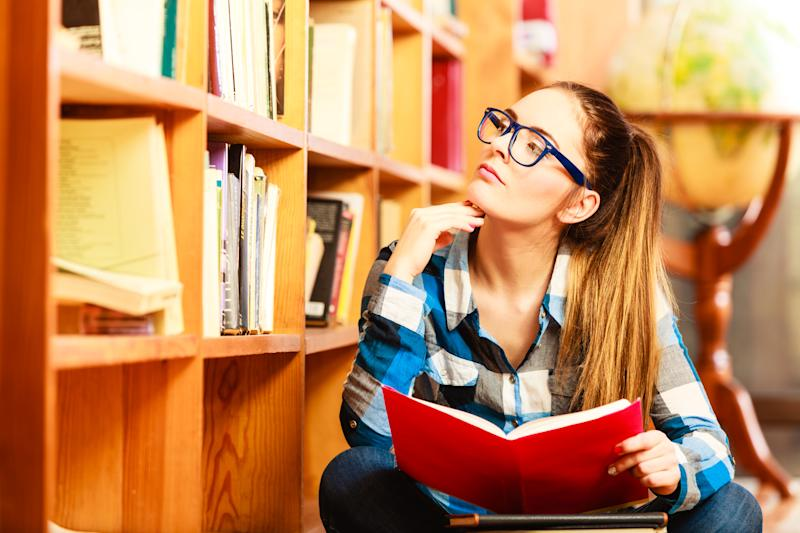 A female college student holding a book while in deep thought in a library.