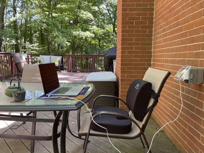 This image provided by Melissa Rayworth shows a lumbar pillow and seat cushion added to an outdoor dining chair to help create a more ergonomic outdoor workspace. Millions of people found themselves working from home during the past year. And many are likely to continue doing so this summer and beyond, even as pandemic restrictions ease. One bonus when working from home: spending some or all of your work day outside. (Melissa Rayworth via AP)