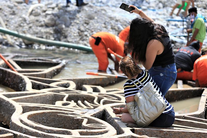 MONTERREY, MEXICO - AUGUST 05: Two girls take a selfie during a visit to pray for the recently unearthed sculpture of the Virigin of Guadalupe at Santa Catarina river on August 5, 2020 in Monterrey, Mexico. At least 400 people went to Santa Catarina river to take stones and water after tropical storm Hanna unearthed sculpture of the Virgin of Guadalupe. (Photo by Medios y Media/Getty Images)