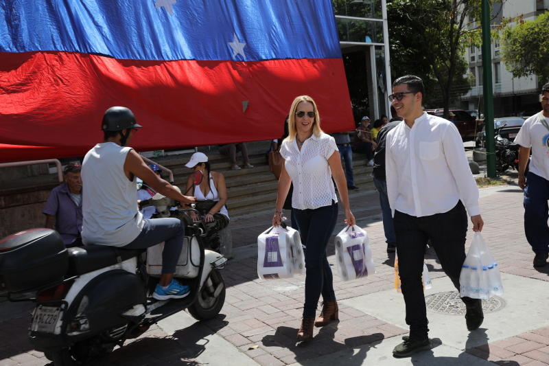 A couple, carrying their purchases of toilet paper and bottled water, walk through a plaza where opponents of the Nicolas Maduro government are gathering for an opposition rally in Caracas, Venezuela, Saturday, May 11, 2019. Opposition leader Juan Guaidó has called for nationwide marches protesting the Maduro government, demanding new elections and the release of jailed opposition lawmakers. (AP Photo/Rodrigo Abd)