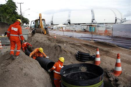 Workers work on areas of infrastructure next to the construction site of the Arena das Dunas stadium, in Natal May 10, 2014. REUTERS/Nuno Guimaraes
