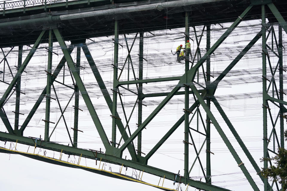 Workers stand on wire mesh below the decking of the Deception Pass Bridge, nearly 1,000-feet long and about 180-feet above the waters below, as work to replace corroded steel and paint the structure continues Thursday, April 29, 2021, in Deception Pass, Wash. Raising state taxes to improve roads and bridges is one of the few things many Republican and Democratic lawmakers have agreed on in recent years. Those efforts have slowed to a crawl this year, even as lawmakers acknowledge a widening gap between needed work and the money to pay for it. (AP Photo/Elaine Thompson)