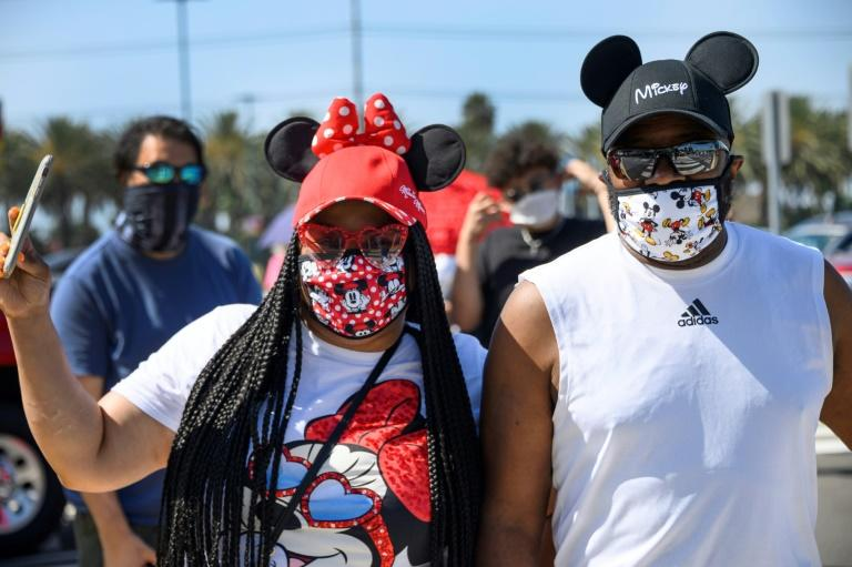 A couple waits in line to enter  Downtown Disney in Anaheim, California the first day the outdoor shopping and dining complex has been open to the public since it closed in mid-March due to COVID-19