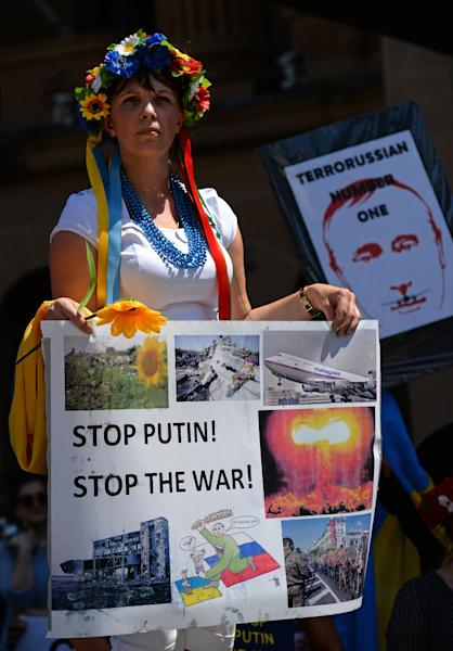 A woman protests against Russia's President Vladimir Putin during a rally against the G20 Leader's Summit in the Australian city of Brisbane on November 15, 2014 (AFP Photo/Greg Wood)