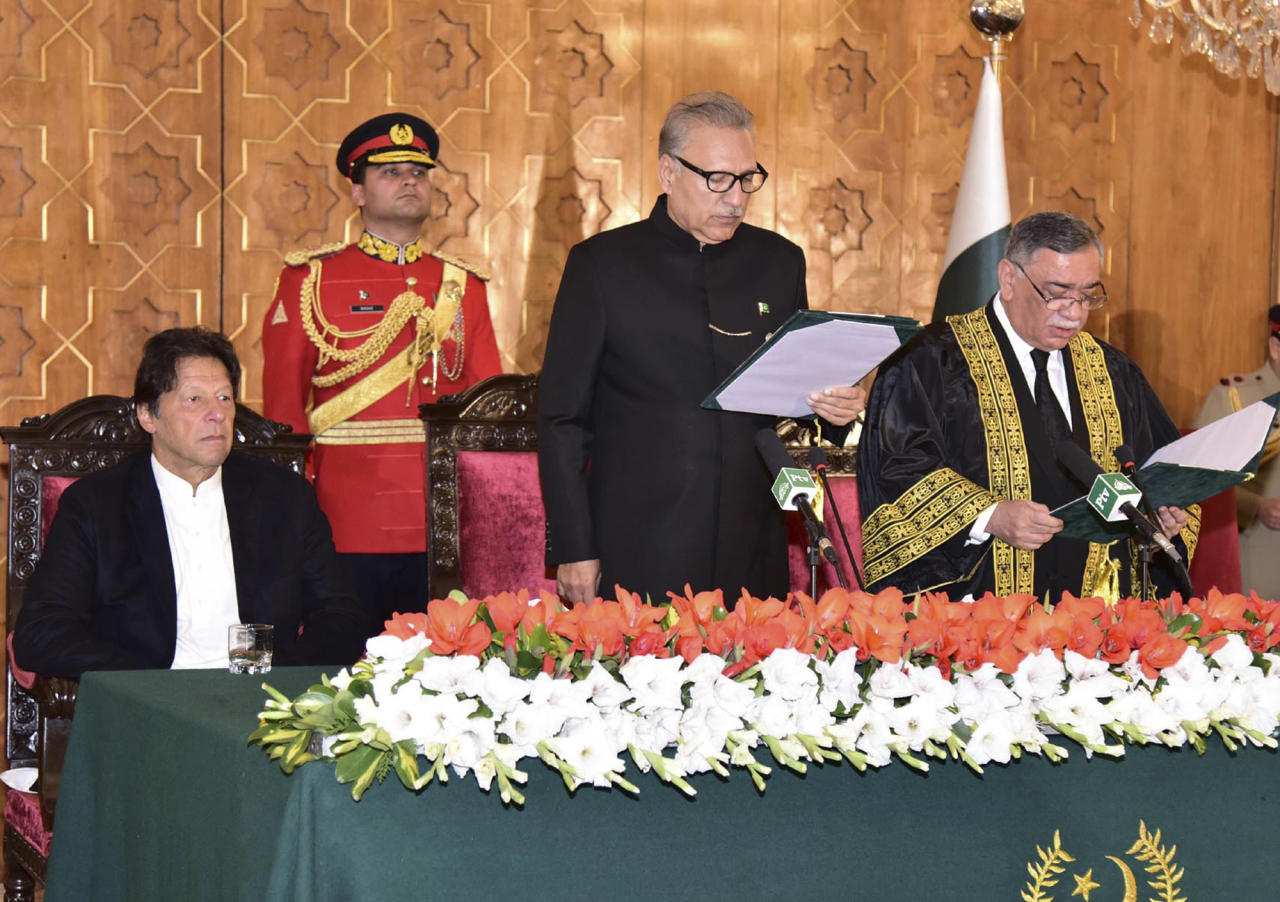 In this photo released by the Press Information Department of Pakistan, President of Pakistan Arif Alvi, center, administers the oath to Asif Saeed Khosa, right, as the country's new chief justice of the Supreme Court in Islamabad, Pakistan, Friday, Jan. 18, 2019. Pakistan's Prime Minister Imran Khan seen on left. (Press Information Department, via AP)