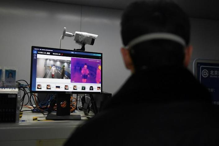 A security guard keeps watch as an AI-powered system screens commuters for fevers while they enter a Beijing metro station (AFP Photo/GREG BAKER)