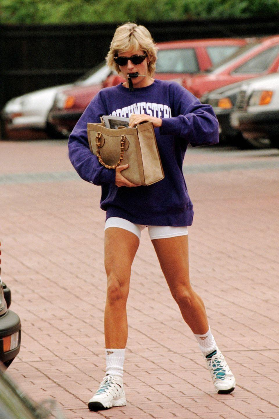 <p>Continuing her penchant for collegiate sweatshirts, Diana represented another American university, sporting a Northwestern sweatshirt and white shorts. Adding some luxury, Diana accessorized with a Gucci tote. </p>