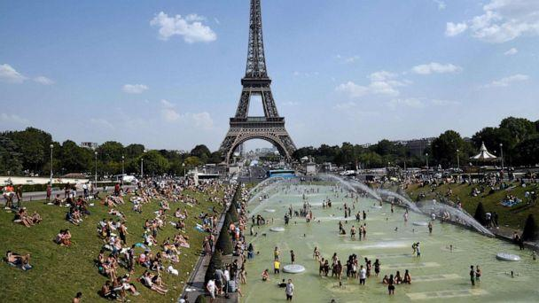 PHOTO: In this file photo taken on July 25, 2019, people cool off and sunbathe by the Trocadero Fountains next to the Eiffel Tower in Paris, as a new heatwave hits the French capital. (Bertrand Guay/AFP/Getty Images, FILE)