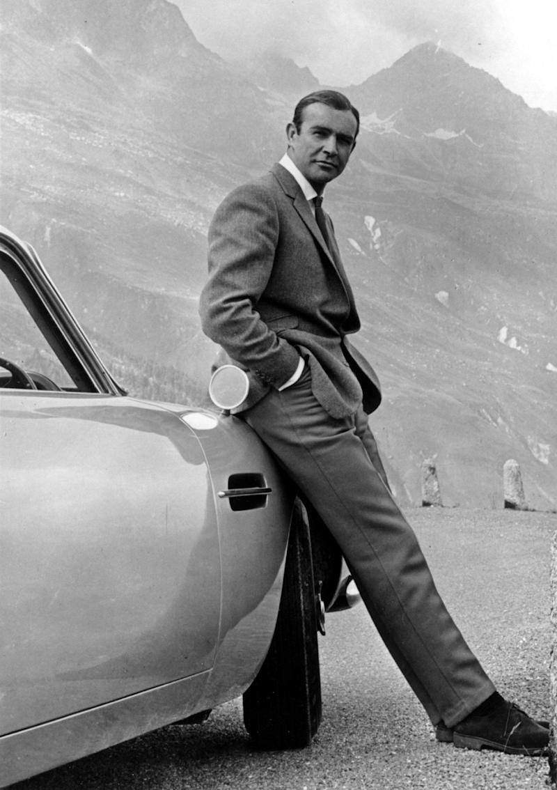 "Actor Sean Connery poses as James Bond next to his Aston Martin DB5 in a scene from the United Artists release ""Goldfinger"" in 1964. (Photo: Michael Ochs Archives via Getty Images)"